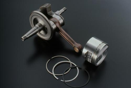 La foto mostra il pistone e il gruppo biella-albero a gomito (composito) del monocilindrico Rotax. Per portare al perno di manovella l'olio che fuoriesce lateralmente da un cuscinetto di banco si impiega un convogliatore centrifugo, ben visibile nell'immagine
