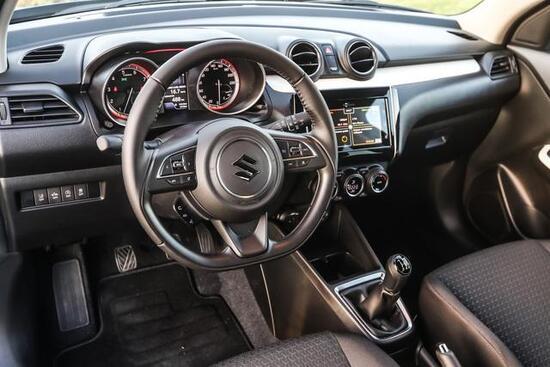 Dentro la Swift 1.2 Hybrid allestimento Top ci sono sedili avvolgenti, modanatura bianca e soprattutto avvisi per la sicurezza di guida
