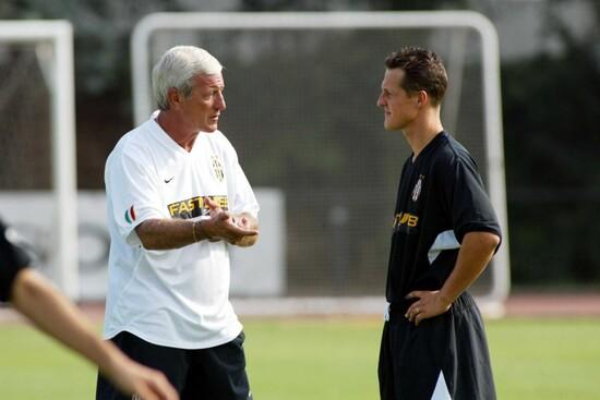 Non solo Formula 1: Schumacher parla con Marcello Lippi in occasione di un allenamento con la Juventus. E' stato per anni attaccante della Nazionale Piloti di calcio