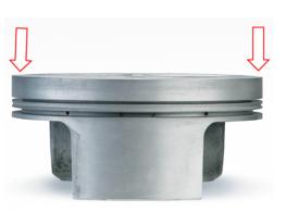 In questa immagine di un pistone di tipo analogo al precedente le frecce servono a dare un'idea di come vengano sollecitate a flessione, sotto la pressione dei gas, le zone del cielo all'esterno delle portate per lo spinotto